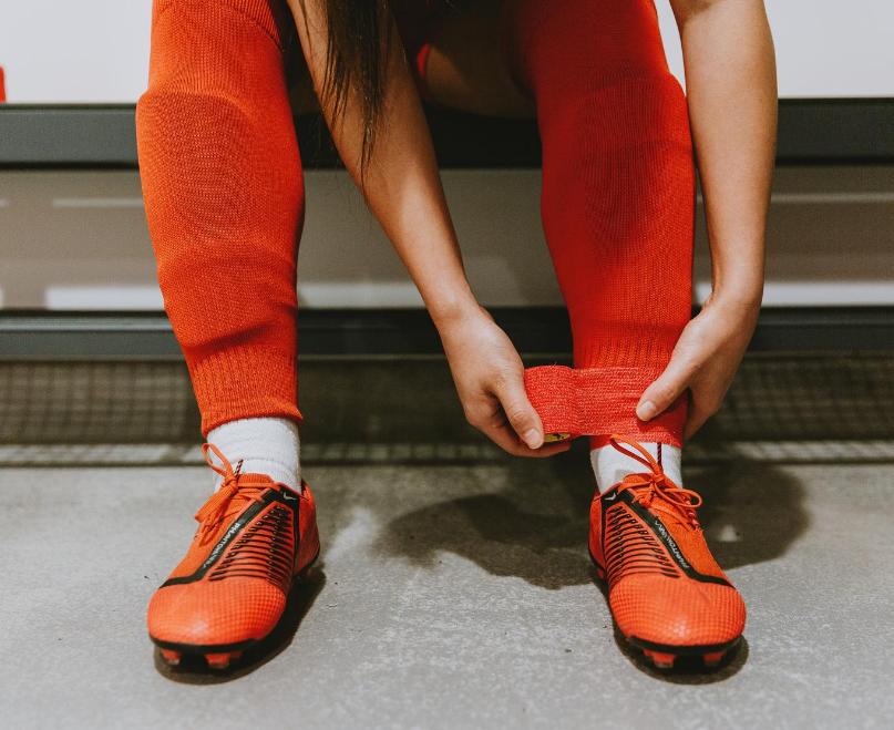 Player uses Cohesive Sock Wrap between cut off socks and team socks