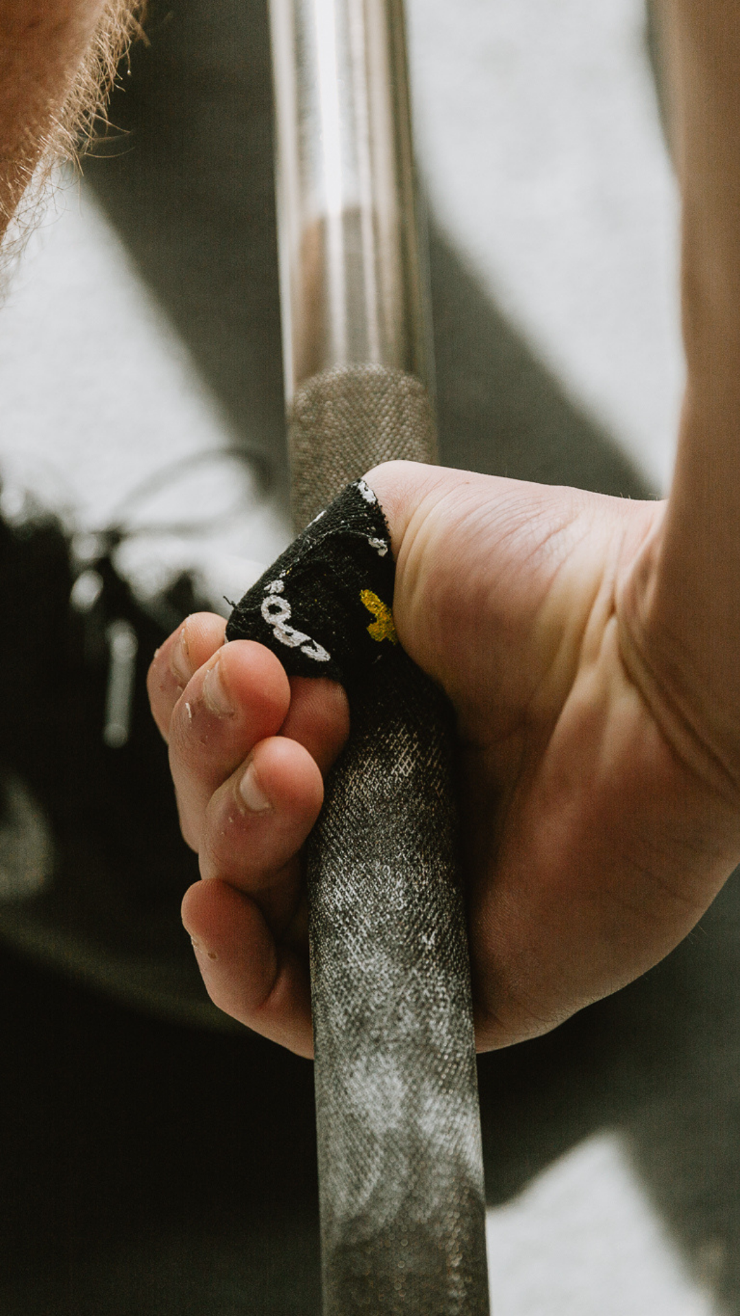 A man lifting weights using the hook grip thumb tape application
